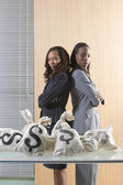 Businesswoman standing proudly beside bags of cash — Stock Photo