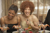 Two young African women laughing at a dinner party — Stock Photo