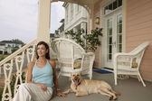 Young woman and her dog on their porch — Stock Photo