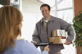 Woman signing for packages from deliveryman — Stock Photo