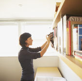 Businesswoman pulling a book from the bookshelf — Stock Photo