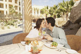 Couple kissing at the table in a resort hotel — Stock Photo