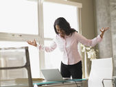 Businesswoman standing at her desk — Stock Photo