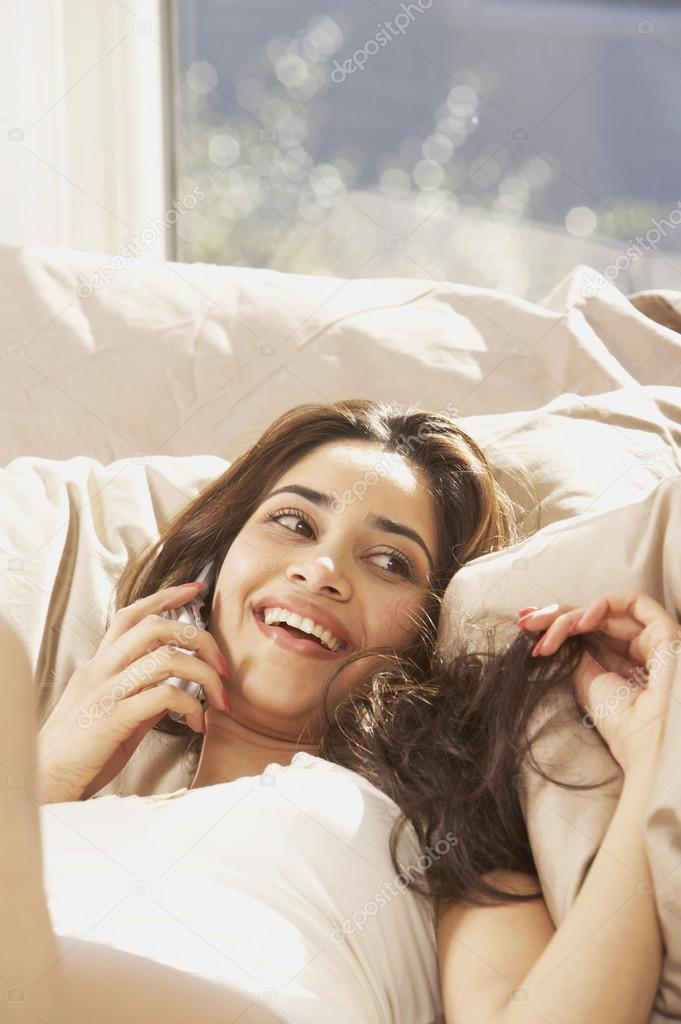 Hispanic woman lying in bed talking on cell phone stock for Cell phone bed