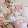 Young girl putting money in piggy bank — Stock Photo #23251110