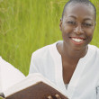African American woman reading book outdoors — Stock Photo #23251124