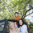 Hispanic grandparents with grandson in jeep — Stock Photo