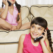 Hispanic sisters using cell phones on sofa — Stock Photo