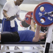 图库照片: Male personal trainer with male client lifting weights