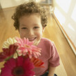 Young boy smiling and offering flowers — Stock Photo