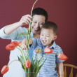 Mother and young son putting flowers in vase — Stock Photo
