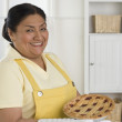 Senior Hispanic woman smiling with pie in kitchen — Stock Photo