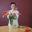 Asian woman putting flowers in vase — Stock Photo