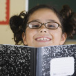 Hispanic girl smiling with notebook in classroom - 图库照片