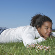 African woman laying in grass smiling — Stock Photo