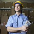 Hispanic male warehouse worker with boxes - Stock Photo