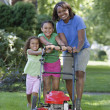 Stock Photo: Africmother and young daughters pushing lawn mower