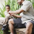 African father and son with fishing gear — Stock Photo