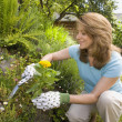 Woman gardening and smiling — Stock Photo