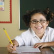 Hispanic girl doing schoolwork in classroom — Stok fotoğraf