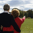 Senior couple hugging and pointing at park — Stock Photo