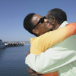 Senior African couple hugging next to water — Stock Photo