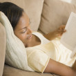 Stock Photo: Africwomlaying on sofreading