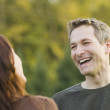 Couple looking at each other and laughing outdoors — Stock Photo