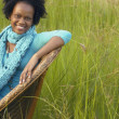 Stock Photo: Young Africwomsitting in chair in field