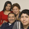 Hispanic grandparents with adult daughter and grandson smiling — Stock Photo