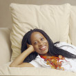 African American woman lying on sofa — Stok fotoğraf