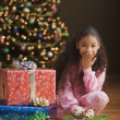 Girl next to stack of gifts on Christmas — Stock Photo