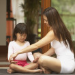 Stock Photo: Asimother teaching young daughter yoga