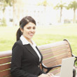 Hispanic businesswoman using laptop on bench outdoors — Stock Photo