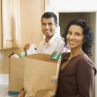 Indian couple unpacking grocery bags in kitchen — Stockfoto