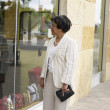 Senior African businesswoman window shopping - Stock Photo