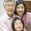 Asian grandmother with daughter and granddaughter smiling — Stock Photo