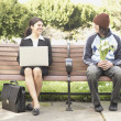 Man with flowers sitting next to businesswoman on bench outdoors — Stockfoto