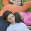 Hispanic family laying in grass — Stock Photo