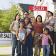 Multi-generational Asian family holding up Sold sign in front of house — Stockfoto