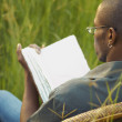 African man reading in field — Stock Photo