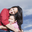 Asian mother and daughter hugging outdoors — Stock Photo