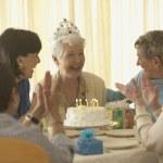 Senior woman celebrating birthday with friends — Stock Photo #23252328