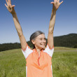 Senior woman in athletic gear with arms raised — Stock Photo