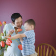 Stock Photo: Mother and young son putting flowers in vase