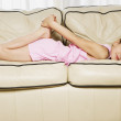 Young Hispanic girl laying on sofa — Stock Photo