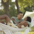 Stock Photo: Middle-aged Africcouple hugging in hammock