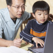 Asian father helping young son with homework — Stock Photo #23252652