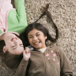 Two girls lying on the floor laughing — Stock Photo #23252700