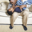 African American father and young son playing on sofa — Stock Photo